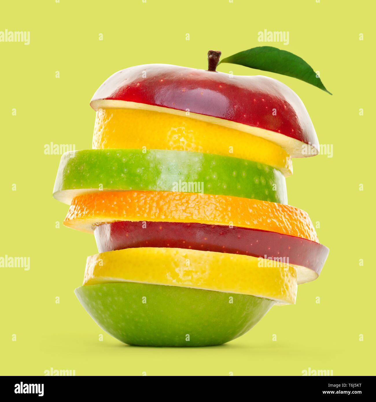 Mixed fruit slices piled up and isolated on green background. Stock Photo