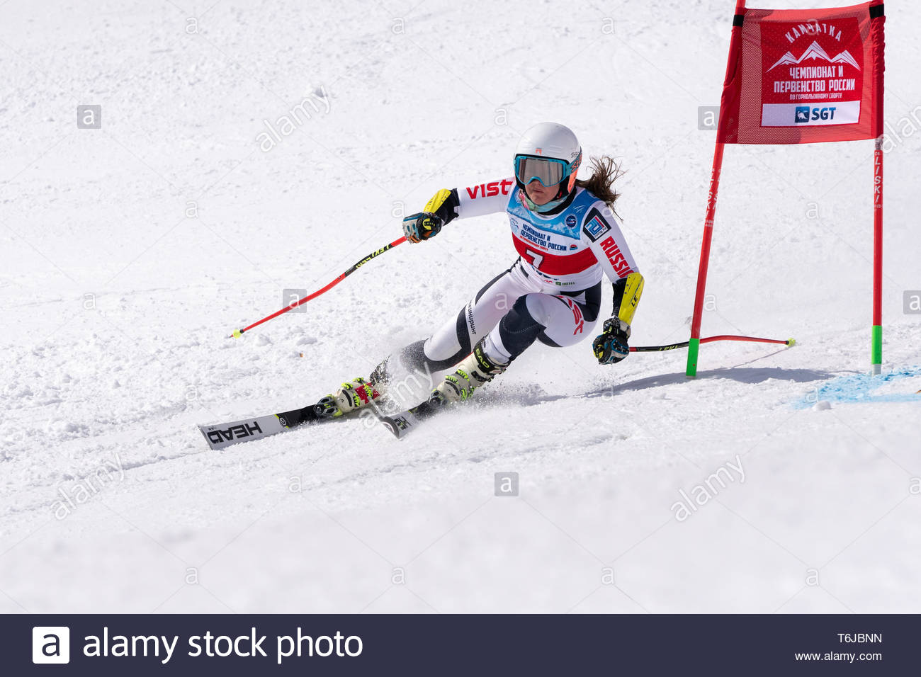 KAMCHATKA PENINSULA, RUSSIAN FEDERATION - APRIL 1, 2019: Mountain skier Popova Ekaterina (Kamchatka Krai) skiing down snowy mountain slope. Russian Wo - Stock Image