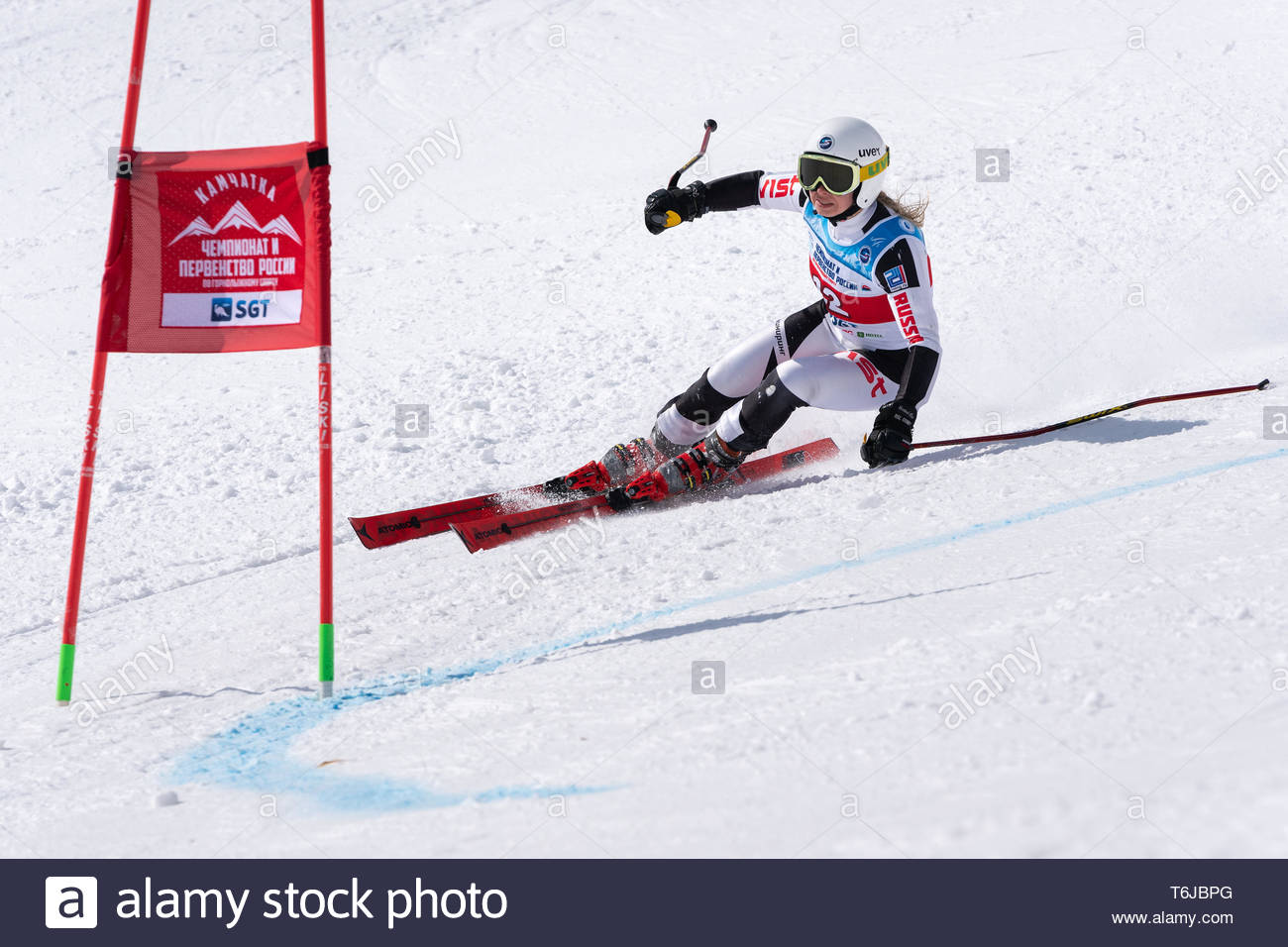 KAMCHATKA PENINSULA, RUSSIAN FEDERATION - APRIL 1, 2019: Mountain skier Kolomova Darya (Krasnoyarsk Region) skiing down snowy mountain slope. Russian  - Stock Image
