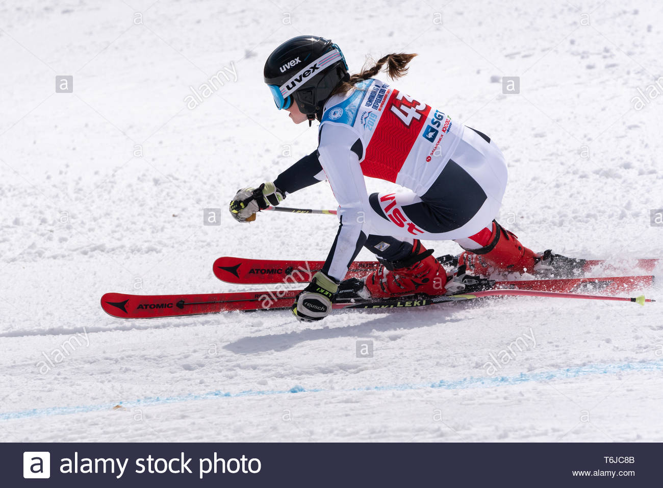 KAMCHATKA PENINSULA, RUSSIAN FEDERATION - APRIL 1, 2019: Mountain skier Ellina Dyachenko (Sakhalin Region) skiing down snowy mountain slope. Russian W - Stock Image