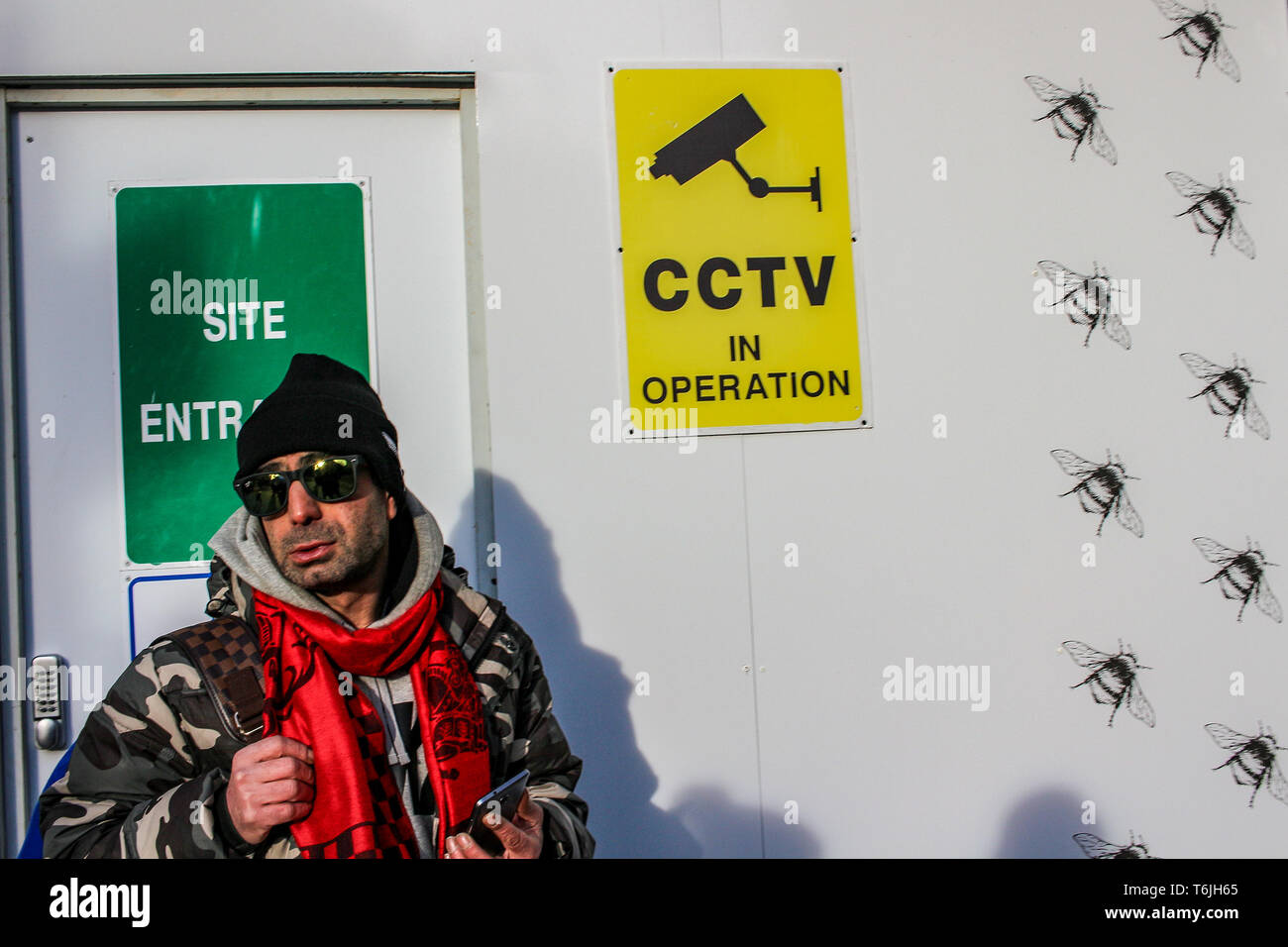 LONDON - FEB 16, 2018: An unidentified man with red scarf and sunglasses next to CCTV Camera Video surveillance sign on site wall. - Stock Image