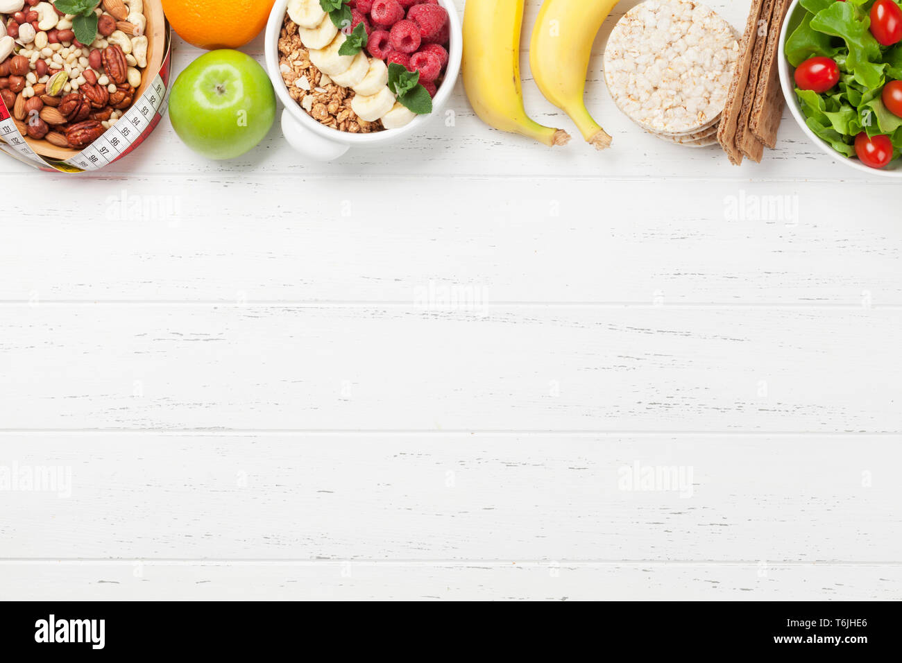 Healthy food and fitness concept. Salad, fruits, vegetables, nuts and breakfast cereal. Top view flat lay with copy space for your text - Stock Image