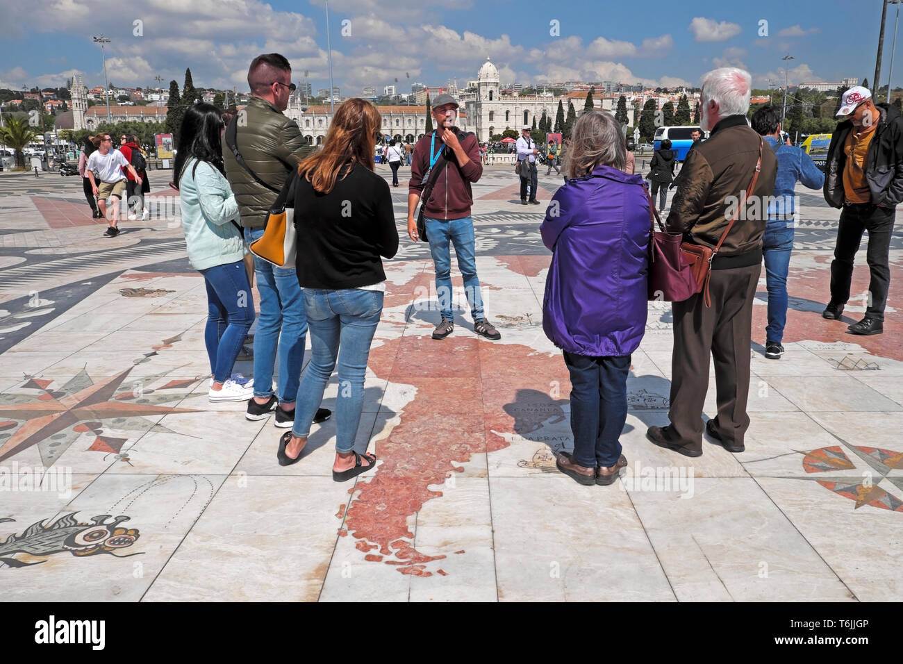Tour guide talking to tourists on the map near Padrao dos Descobrimentos Monument to the Discoveries Lisbon Lisboa Portugal Europe EU KATHY DEWITT - Stock Image