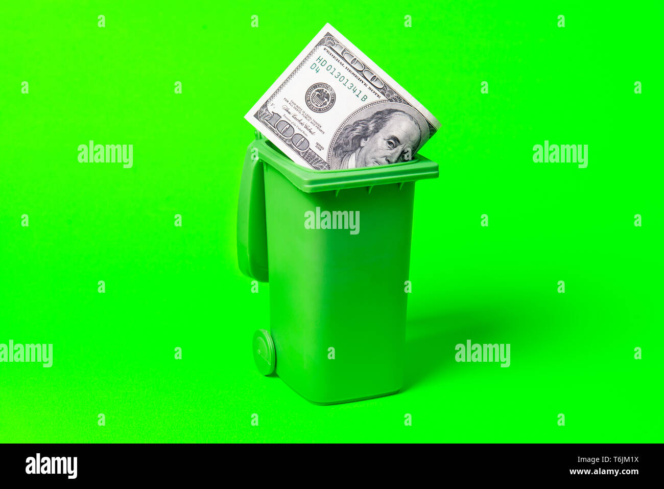 Money trash can isolated on green background. - Stock Image