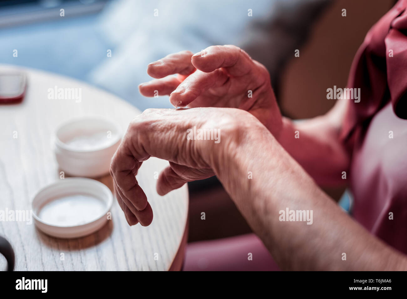 Gentle old woman wearing pink blouse and treating her hands - Stock Image