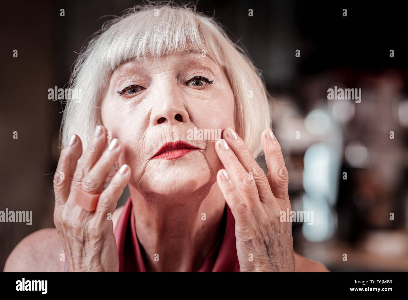 Gentle blonde senior lady covering skin on her face - Stock Image