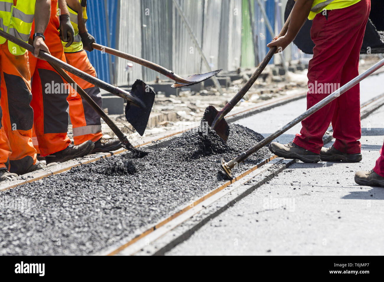 Workers construct asphalt road and railroad lines - Stock Image