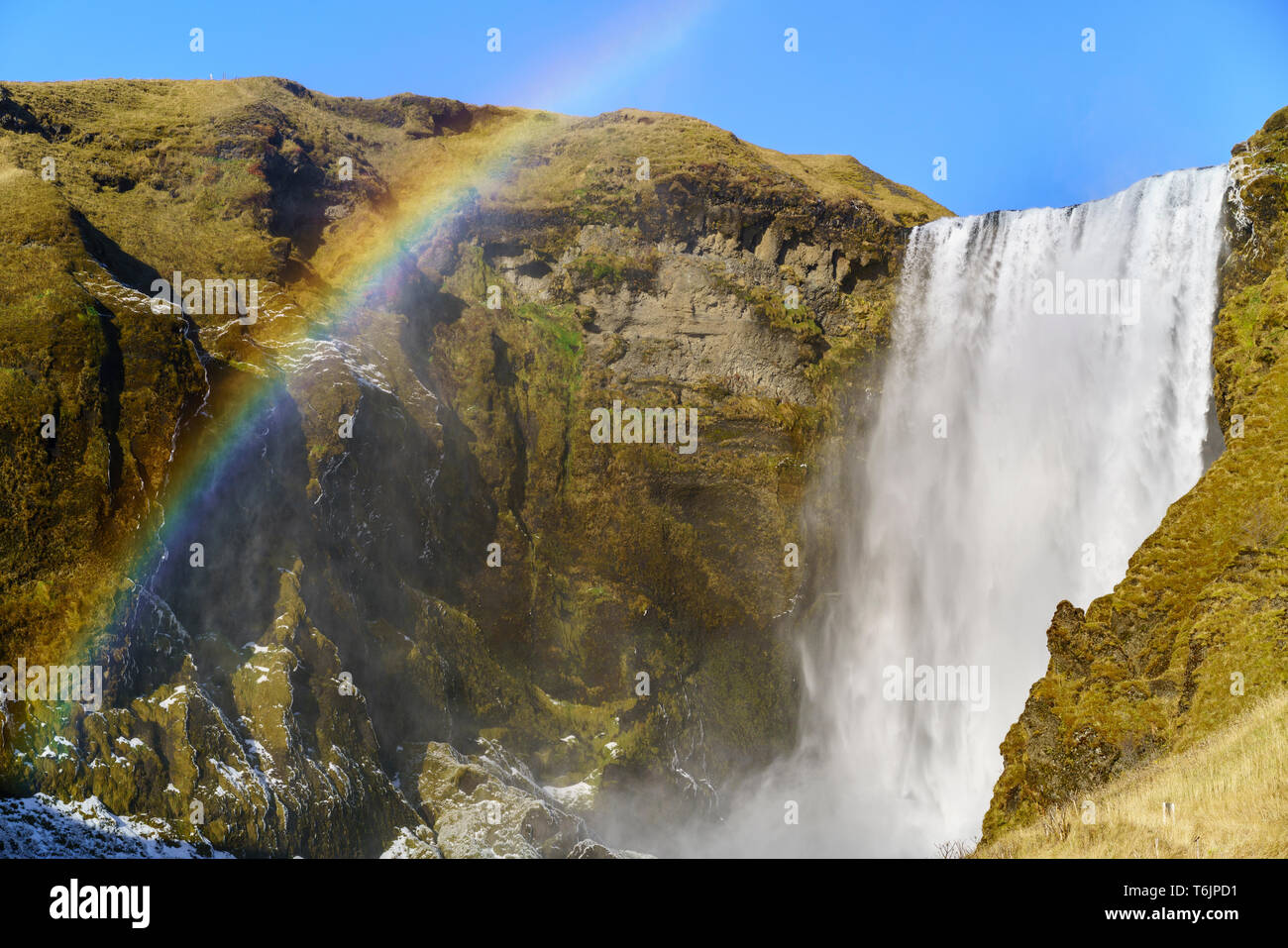 View of the impressing Skógafoss with its rainbow - Stock Image