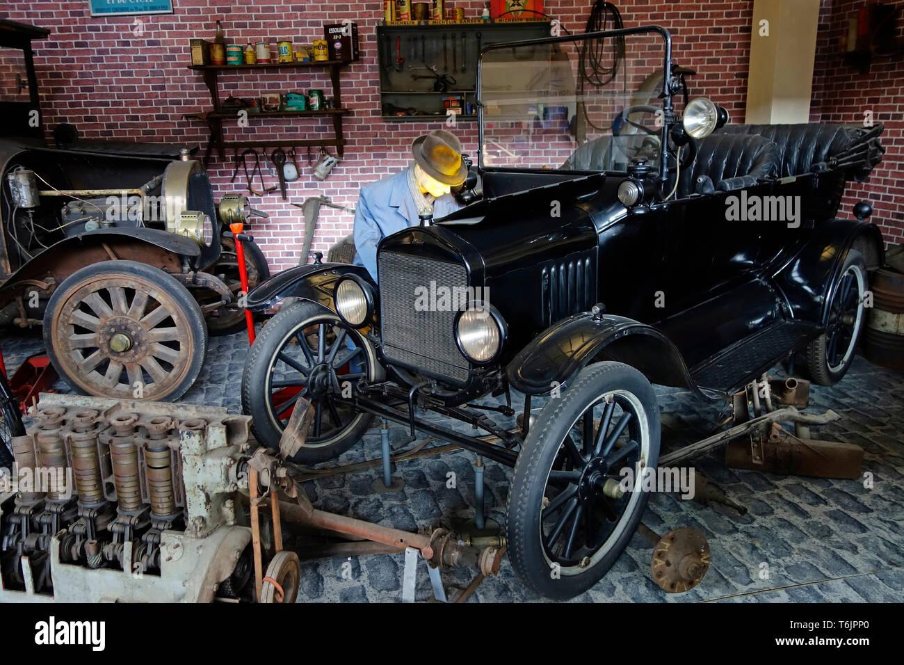 Diorama showing garage owner restoring on 1921 Ford Model T oldtimer in workshop at Autoworld, vintage car museum in Brussels, Belgium - Stock Image