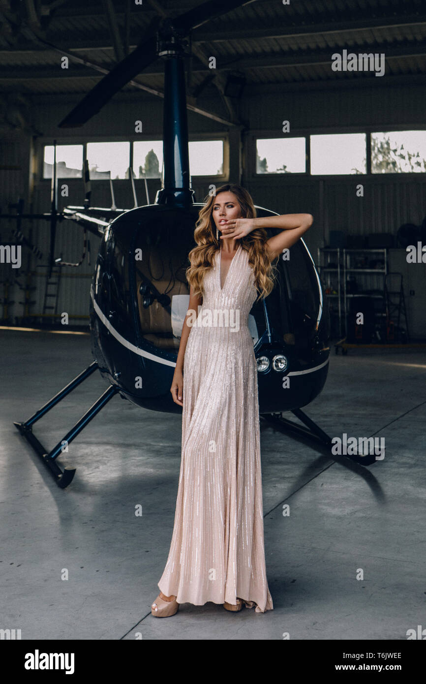 Tender young lady in amazing fashionable dress standing in hangar near the black helicopter. Long evening pink dress, high heel shoes and accessories. Stock Photo