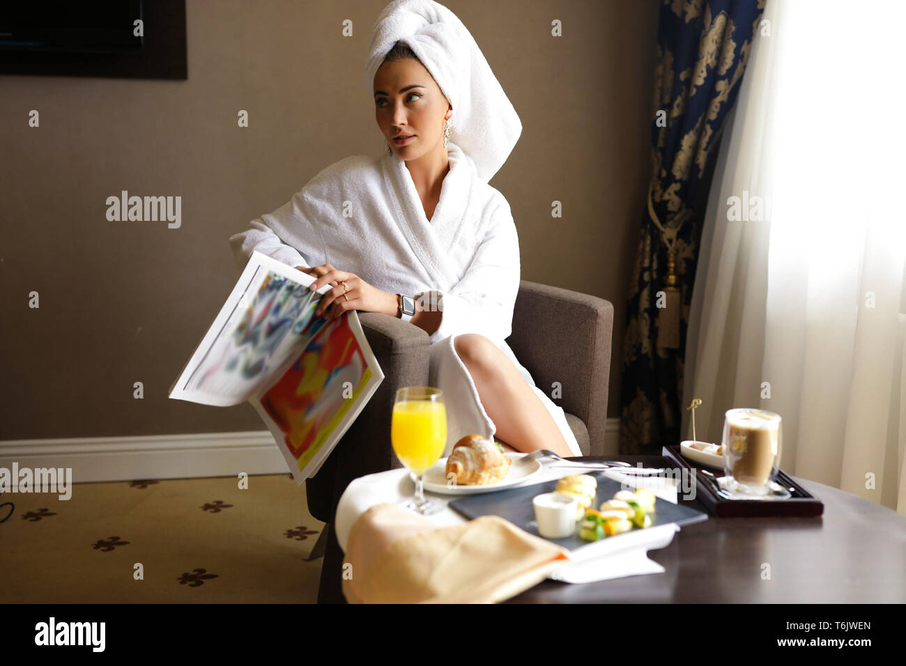 Picture of fancy woman having rest in luxury five stars hotel. Soft white towels and bathrobe, stylish interior. Sitting in a comfortable chair, hold Stock Photo