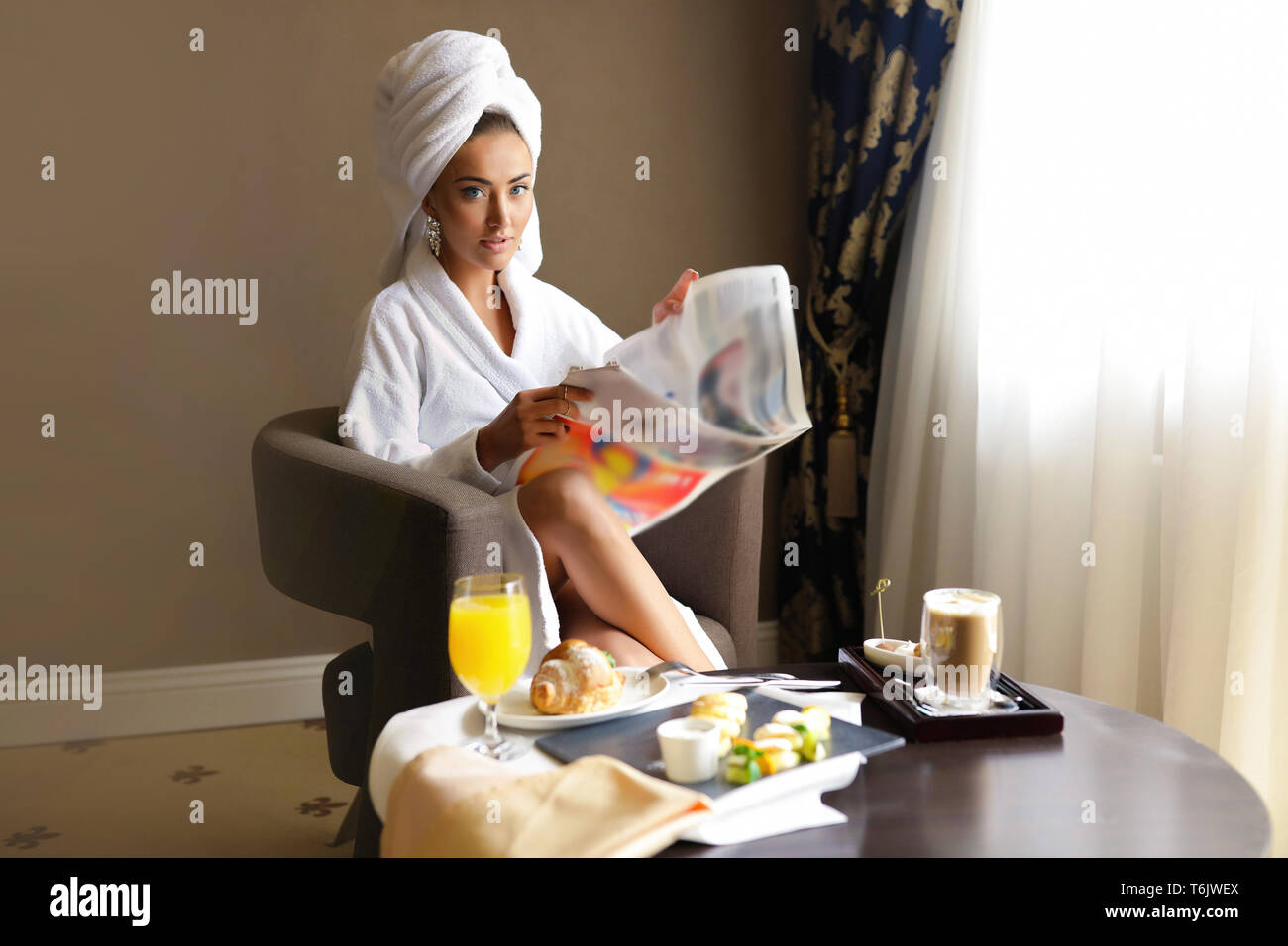 Slim tender girl sitting in a hotel room by herself, relaxing after morning spa. Reading newspaper and have a breakfast with fresh juice and croissant Stock Photo