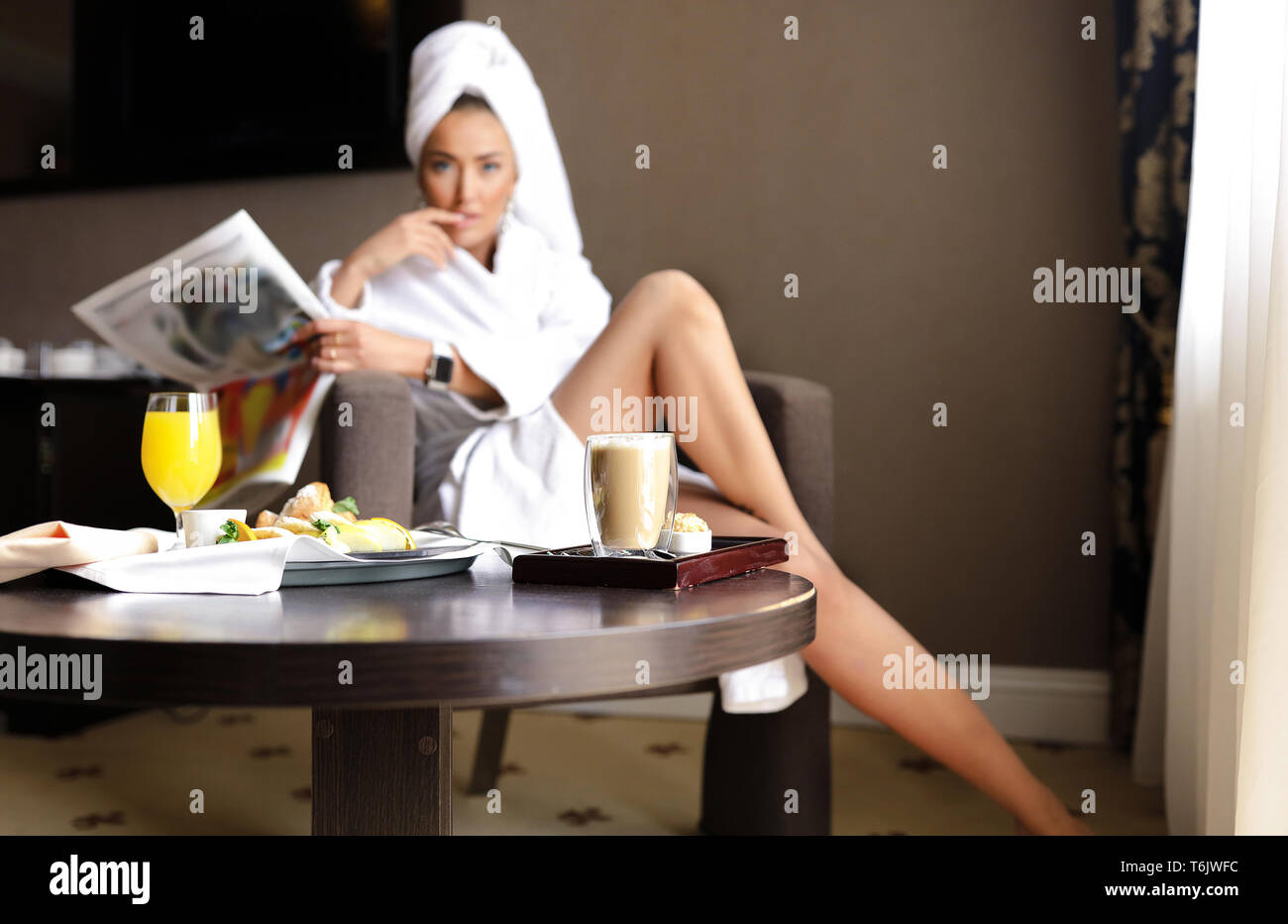 Young beautiful woman relaxing in the hotel room in the chair with the newspaper and fresh tasty breakfast. Orange juice, coffee, croissant and desert Stock Photo
