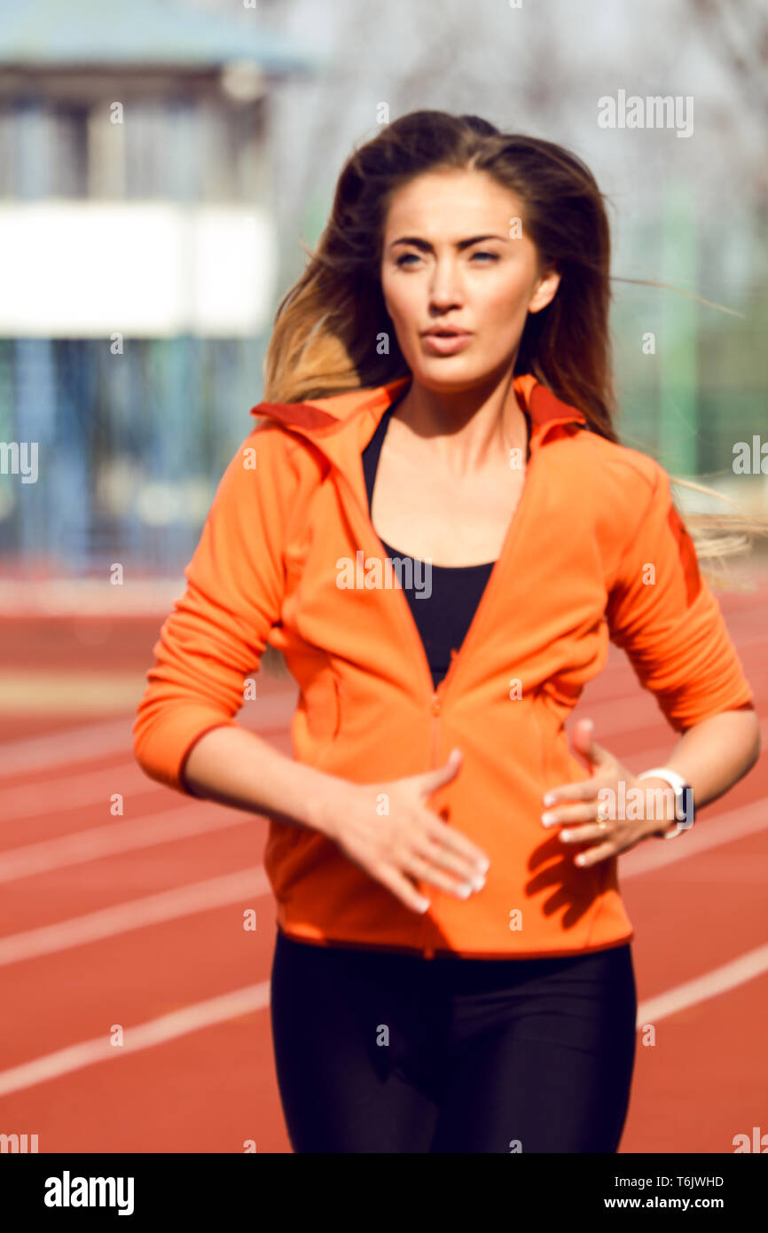 Pretty athlete girl running on the stadium in the morning. Long beautiful hair waving. Wearing comfortable orange jacket and black leggins. Sunny day Stock Photo