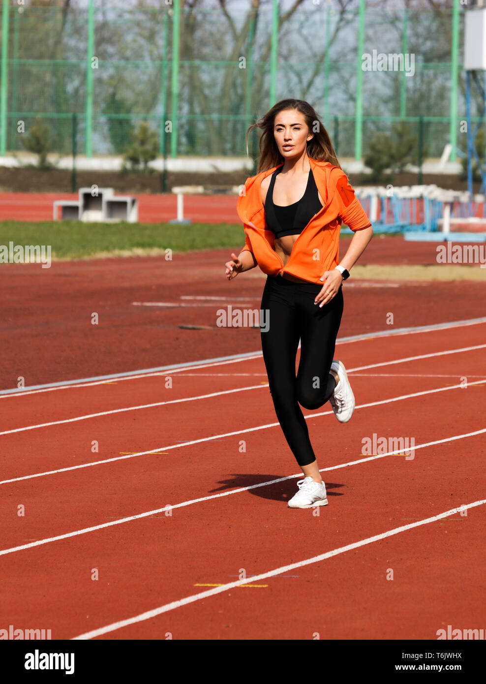 Summer morning workout outdoor on the sport stadium. Young woman running on the track, preparing for the marathon.Comfortable and modern black leggins Stock Photo