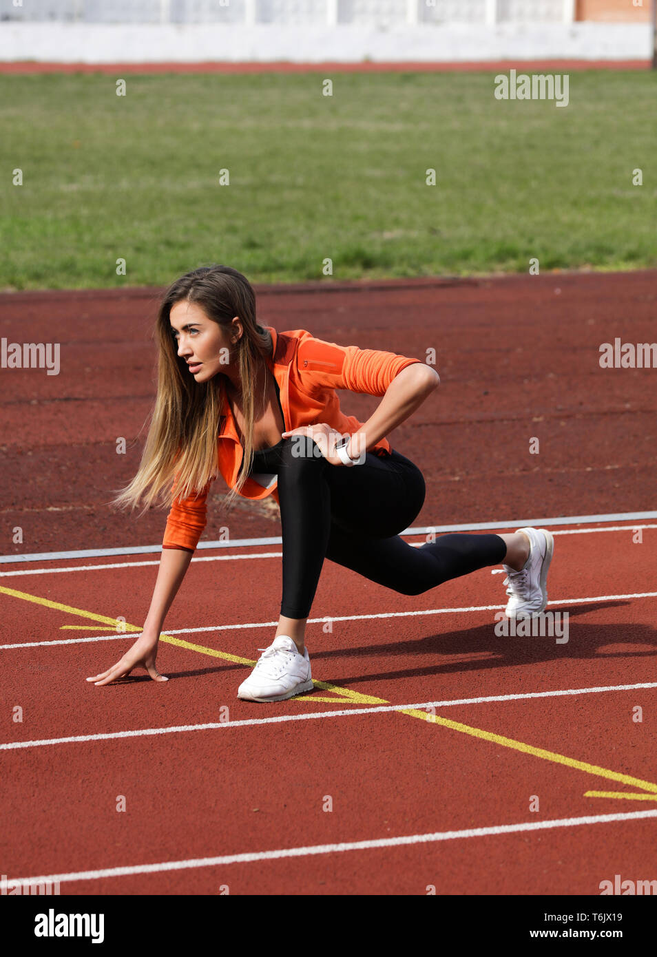 Active athlete preparing to the marathon on the track.Doing stretching and warm up to get to the finish first.Wearing fashionable, comfortable clothes Stock Photo