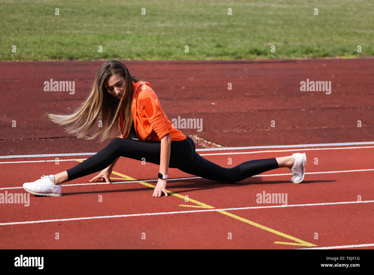Slim blonde doing stretching outdoor on the stadium. Wearing modern and comfortable sportswear, orange jacket, white sneakers and black leggins. Long Stock Photo
