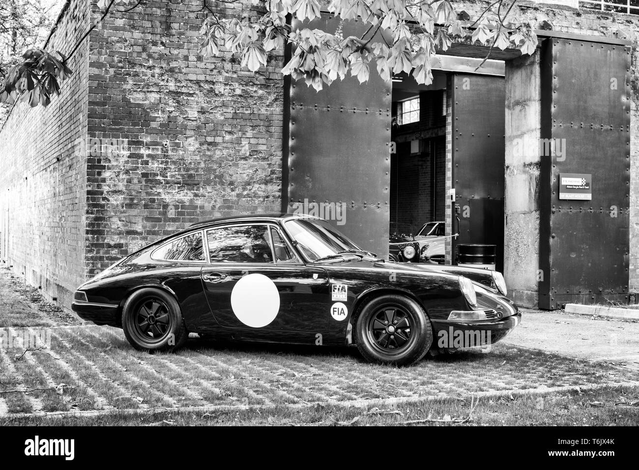 1965 Porsche 911 SWB Competition Car in front of a workshop at Bicester heritage centre 'Drive It Day'.Bicester, Oxfordshire, England. Black and White - Stock Image