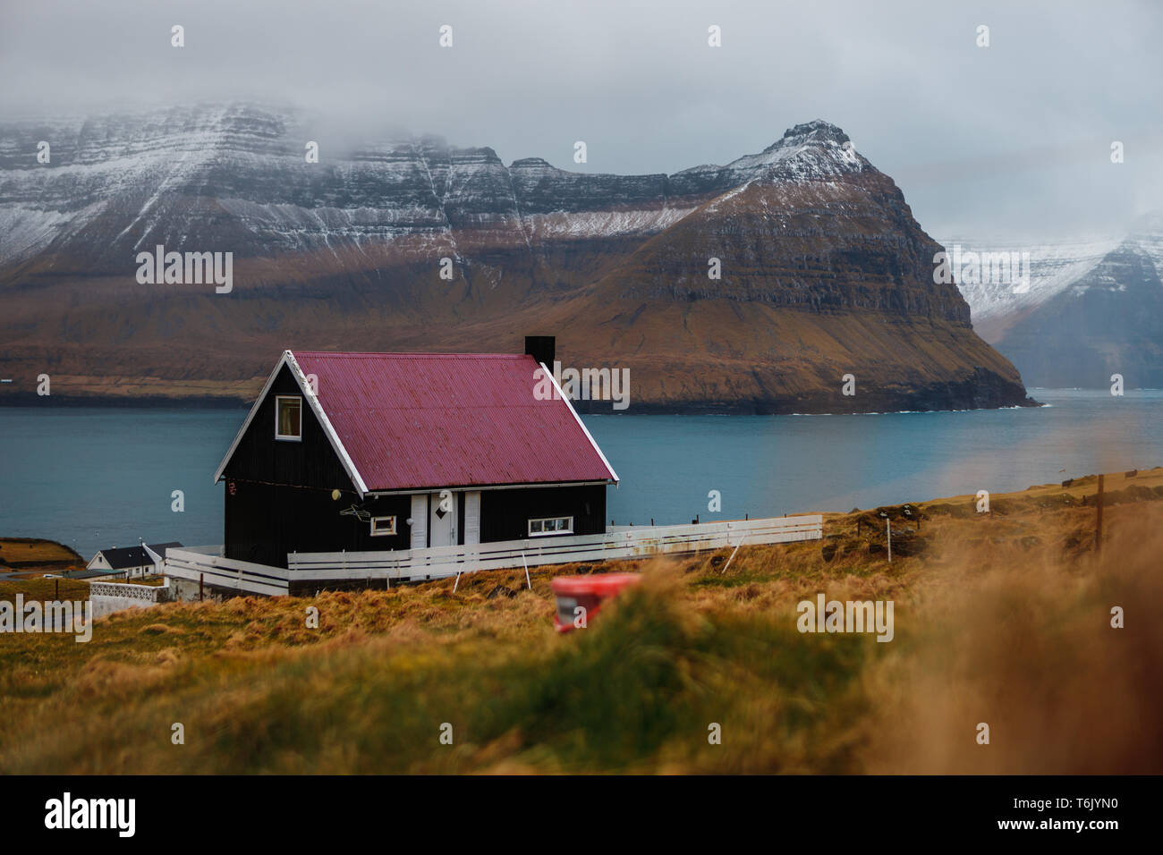 Typical Faroese black wooden house with colourful roof in the village Viðareiði with snow-covered peaks of Kunoy and Kalsoy island (Faroe Islands) - Stock Image