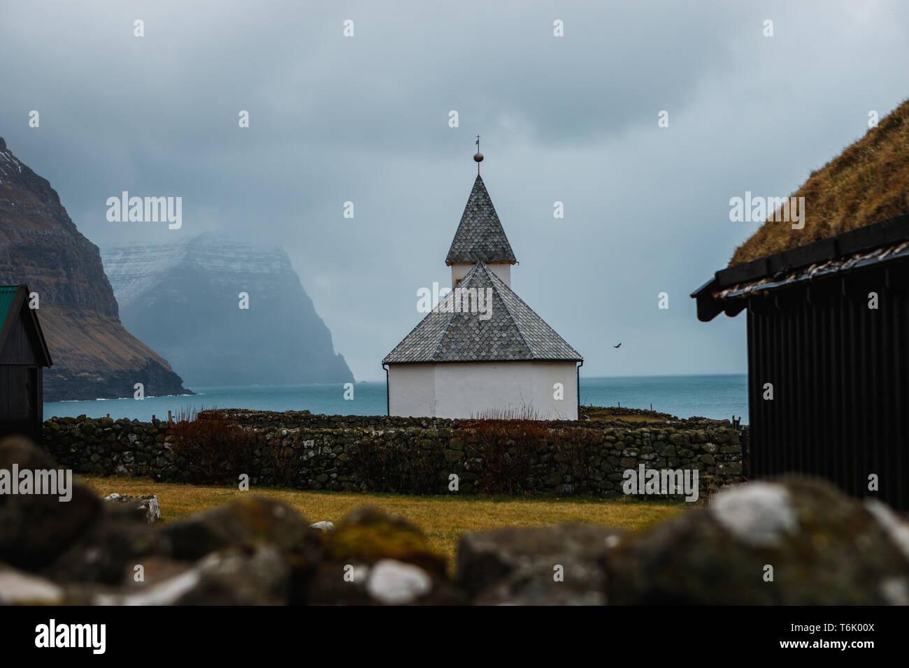 View onto the church of Viðareiði (Viðareiði Kirkja) with moody cloudy sky, fog and snow-covered mountains (Faroe Islands, Denmark, Europe) - Stock Image