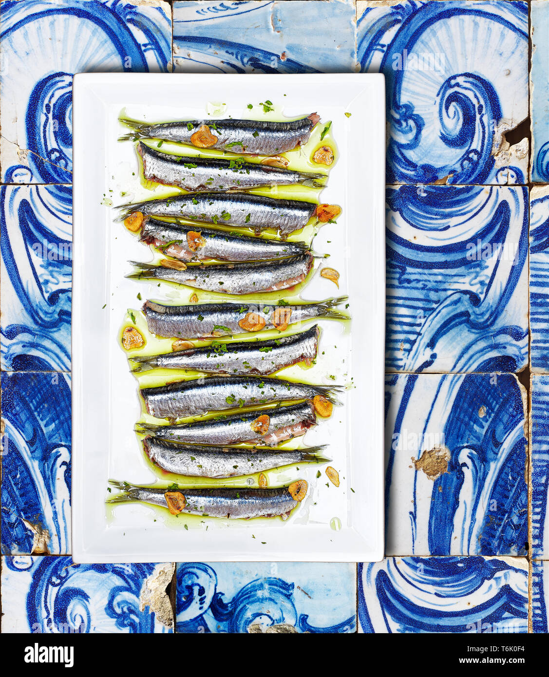Anchovies cooked Basque Country style on a white plate over a tiled background. - Stock Image