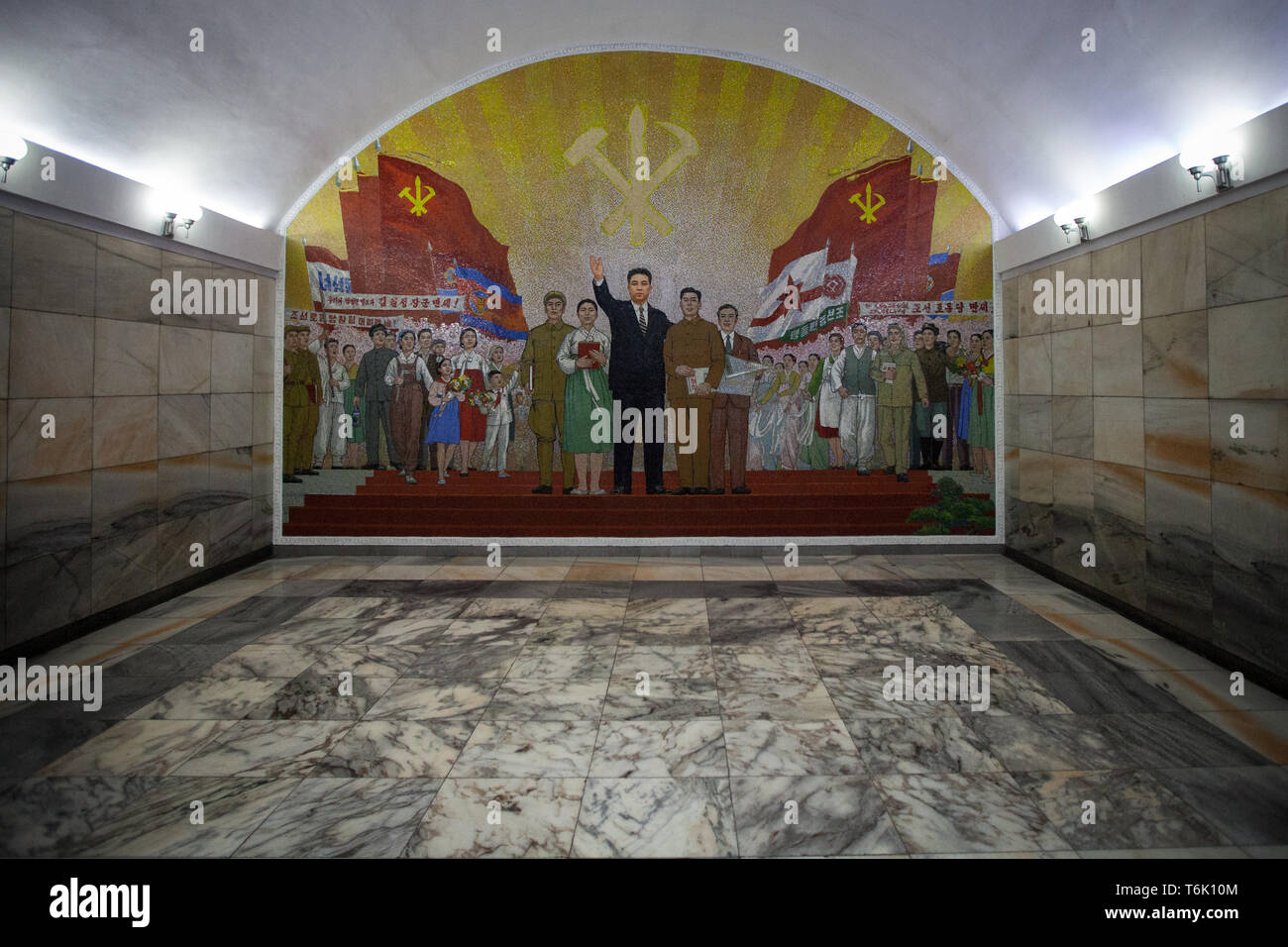 A large mosaic mural inside a Pyongyang metro station shows flags and workers and the symbol of the North Korean Communist Party. - Stock Image