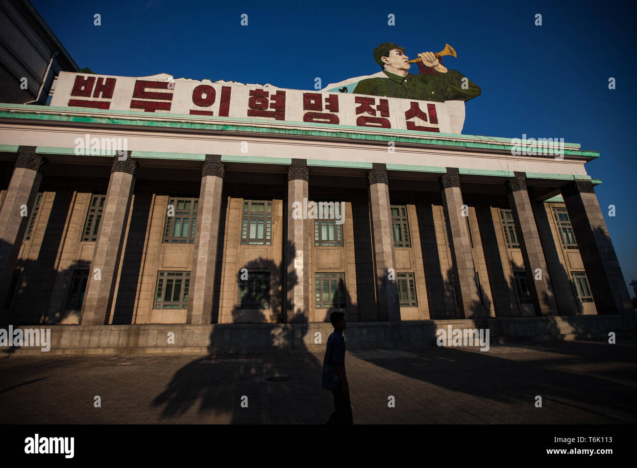 A building on the corner of Kim Il Sung Square in Pyongyang has a large image of a bugler with messages on the roof. Stock Photo