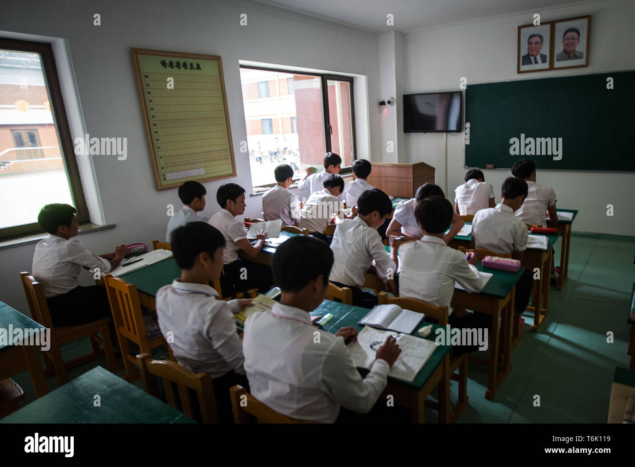 Portraits of Kim Il Sung and Kim Jong Il in a classroom of children in Pyongyang, North Korea. - Stock Image
