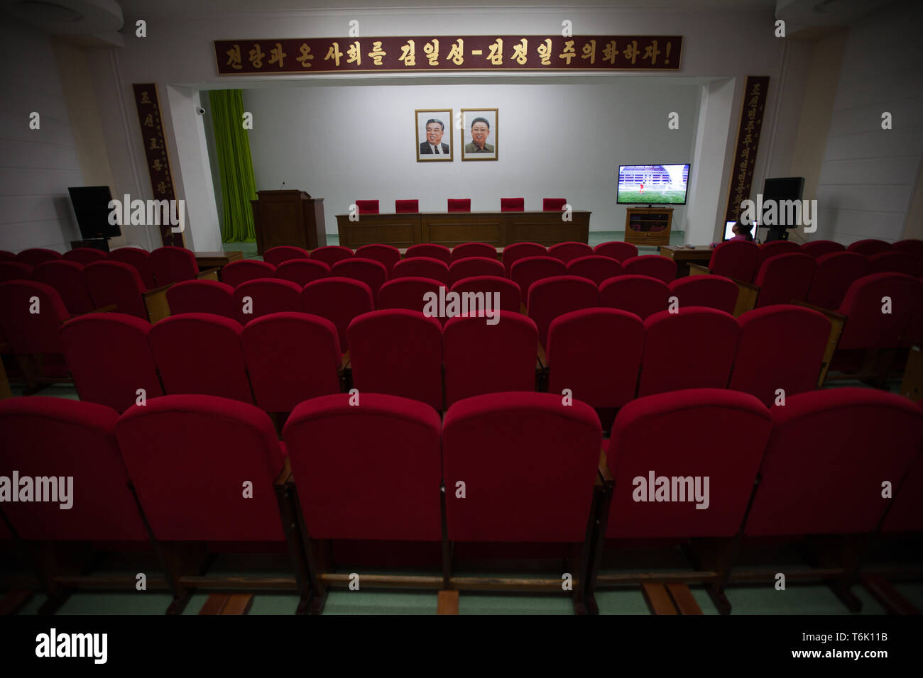 Portraits of Kim Il Sung and Kim Jong Il adorn the wall above a lecture theatre in Pyongyang. - Stock Image