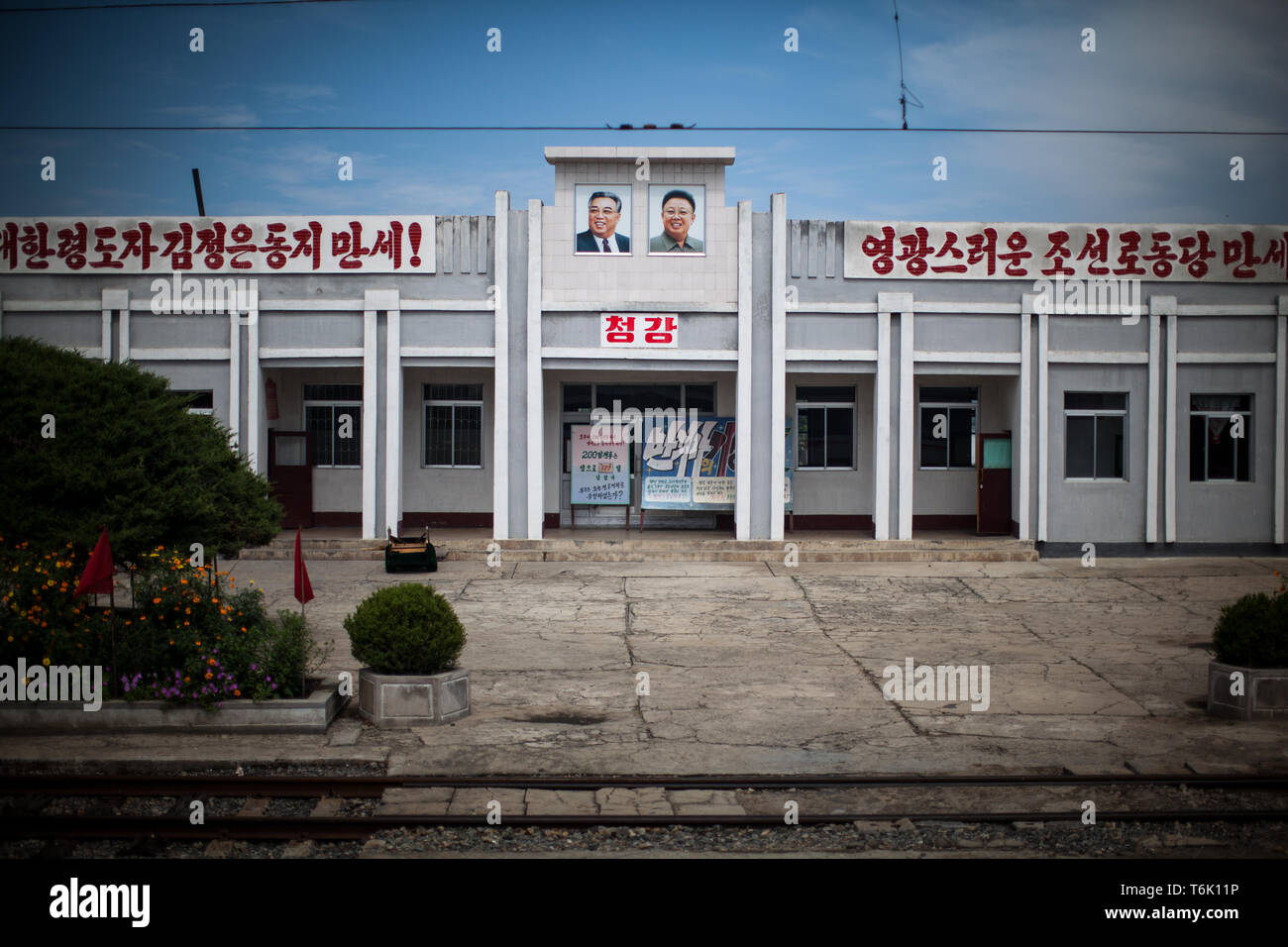 Portraits of Kim Il Sung and Kim Jong Il at a railway station in North Korea. - Stock Image
