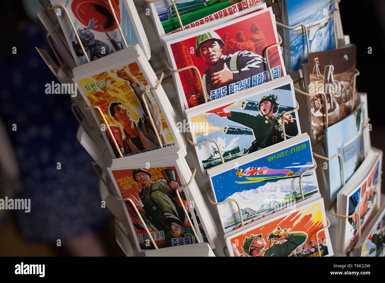 Postcards for sale to tourists in DPRK with graphic propaganda and political messages. - Stock Image