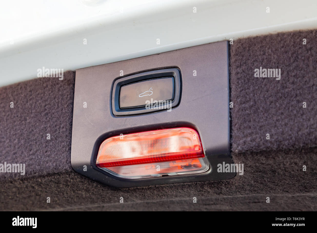 Interior view with electric trunk adjustment button with red and white reflector lamp of luxury very expensive new beige car after cleaning in the veh - Stock Image