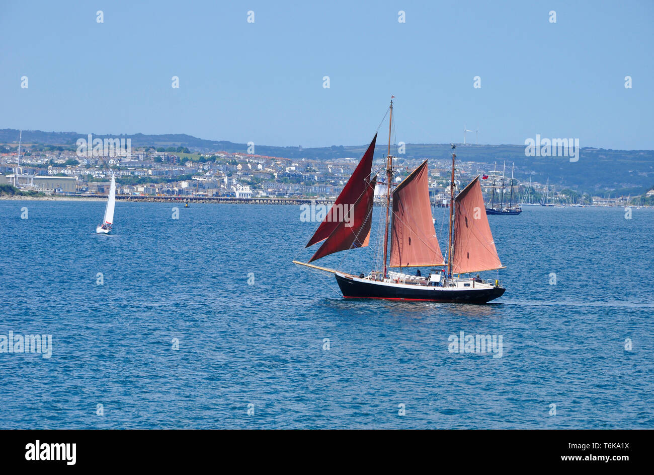 Two masted schooner with red sails in Carrick Roads off Falmouth in Cornwall, England,UK - Stock Image