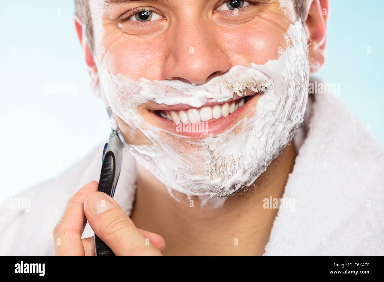 Health beauty and skin care concept. Handsome young bearded man with foam on face shaving with razor on blue background. - Stock Image