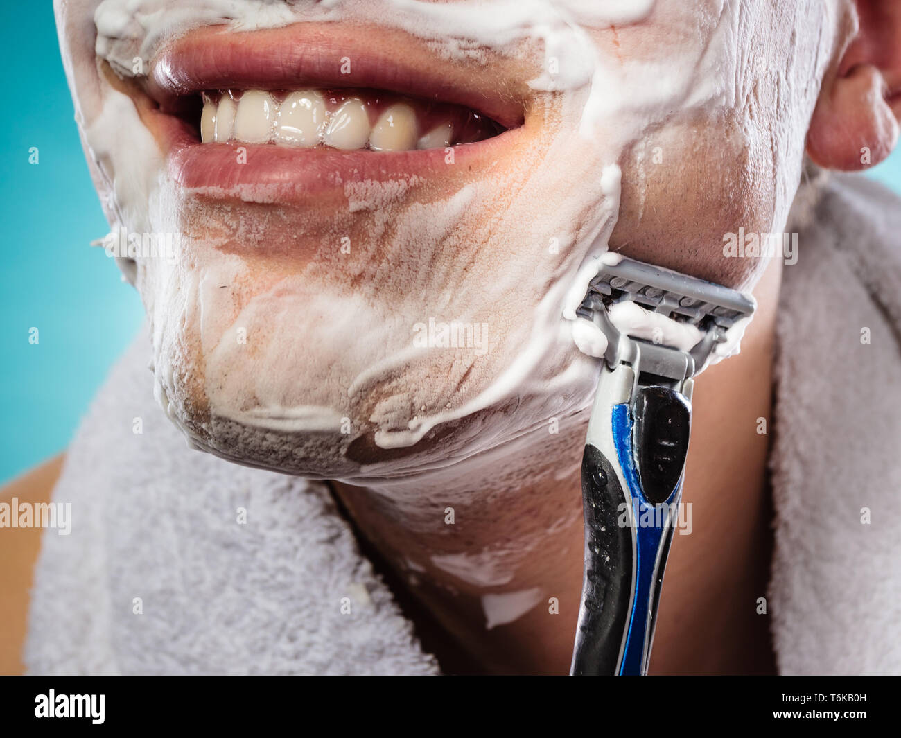 Health beauty and skin care concept. Handsome young bearded man with foam on face shaving with razor on blue background. Unusual wide angle view - Stock Image