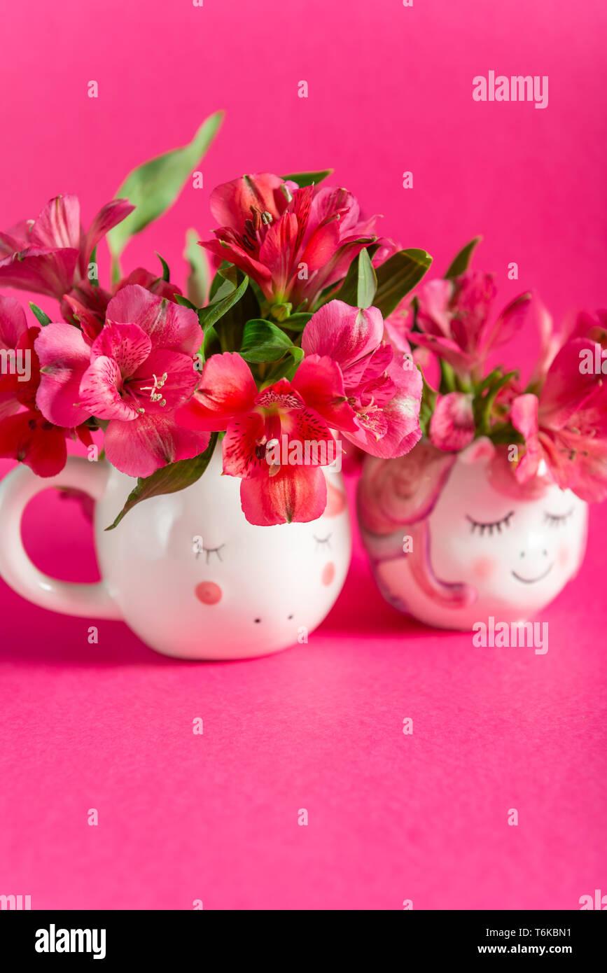 Unicorn mugs with Alstroemeria on bright pink background - Stock Image