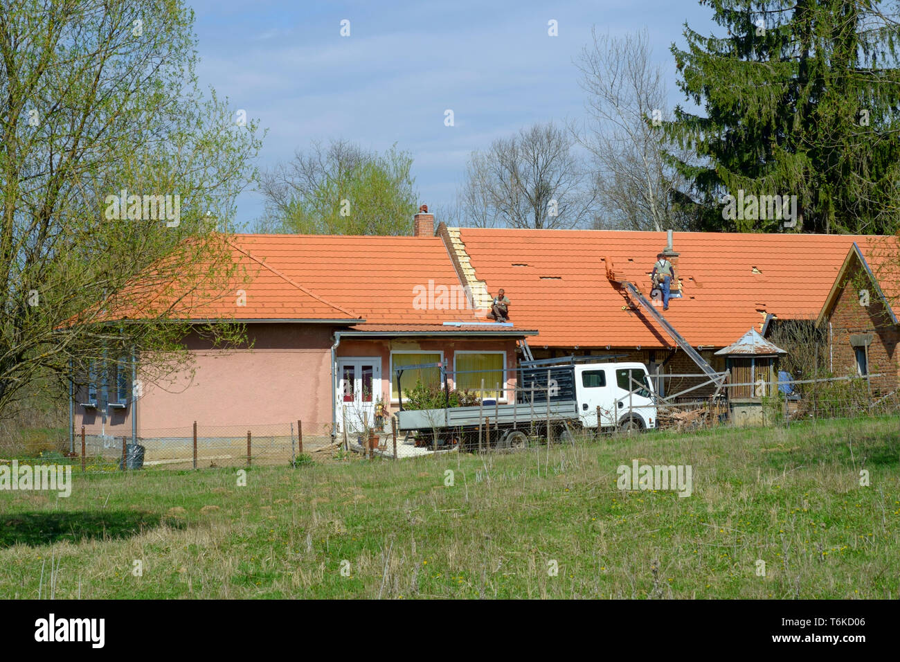 workmen finishing off replacing the roof on a rural hungarian village house zala county hungary Stock Photo