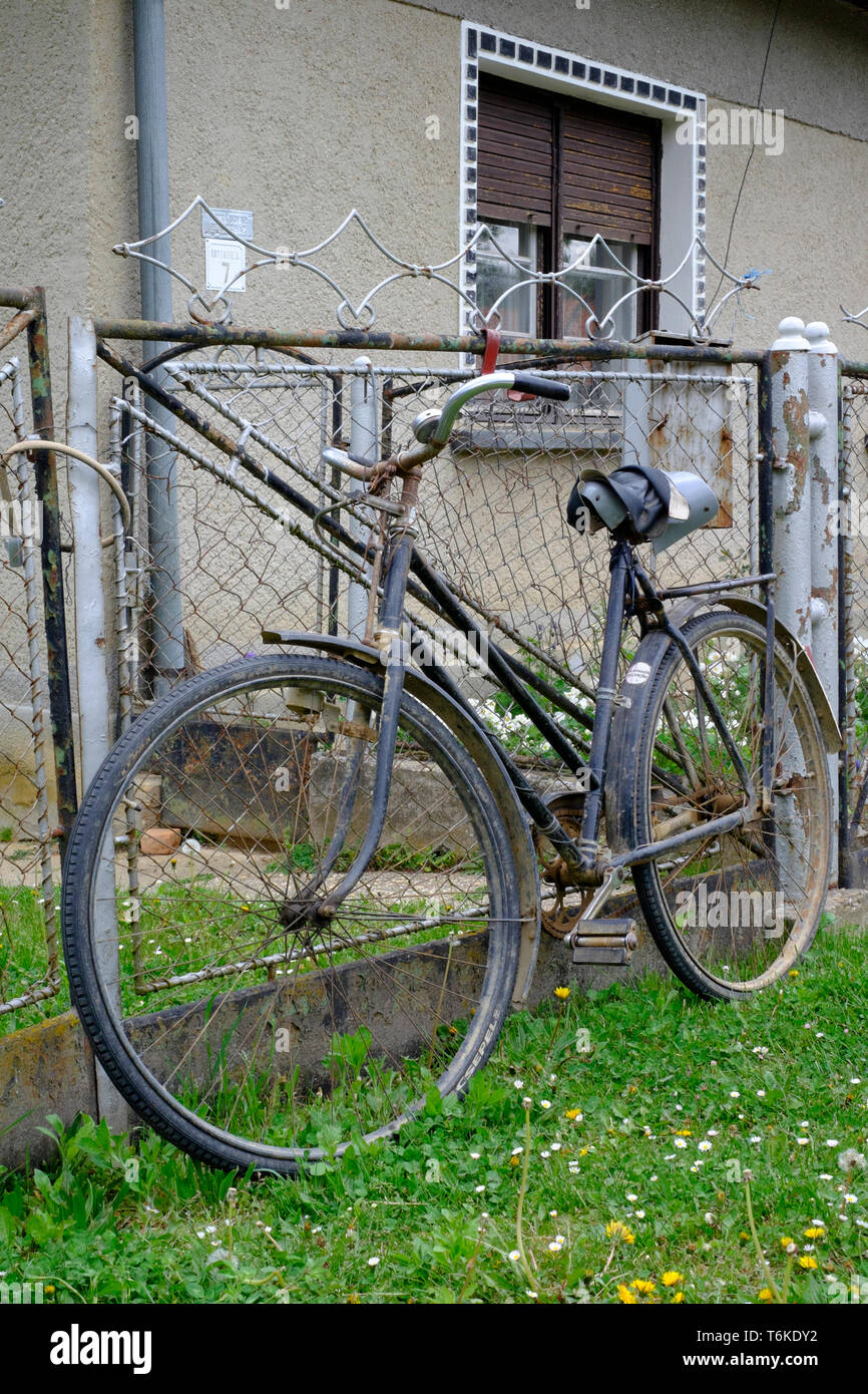 old fashioned bicycle propped against a fence in a rural village zala county hungary Stock Photo