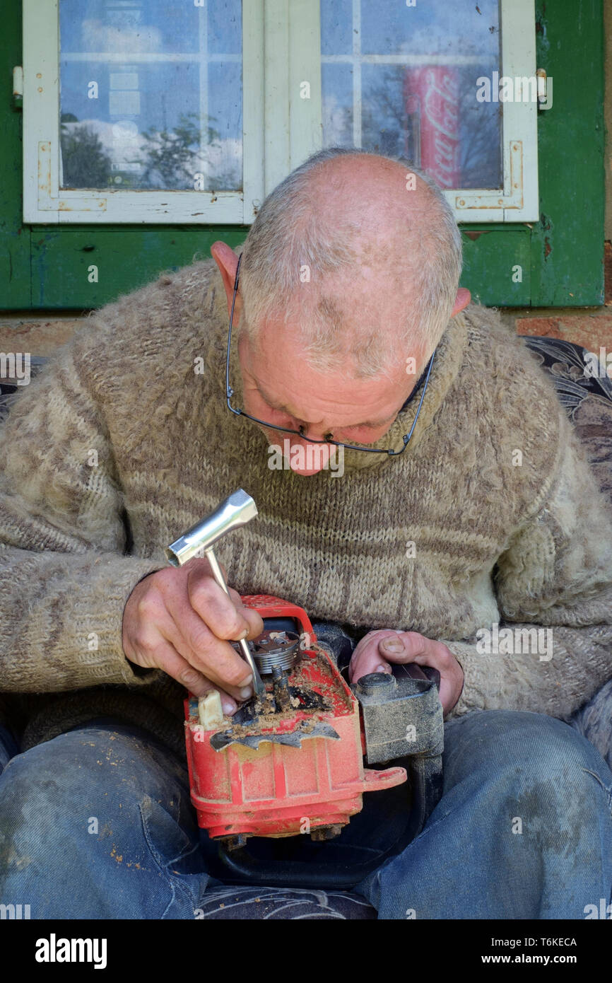mature man working on a chainsaw to replace the blunt chain with a sharp one zala county hungary Stock Photo