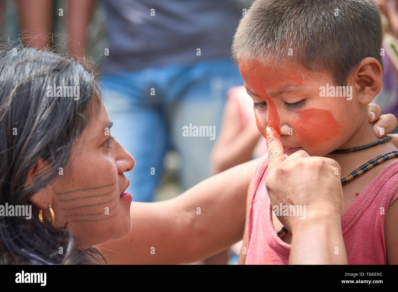 A woman paints a child's face with urucum before a march by indigenous people through the streets of Atalaia do Norte in Brazil's Amazon region. - Stock Image
