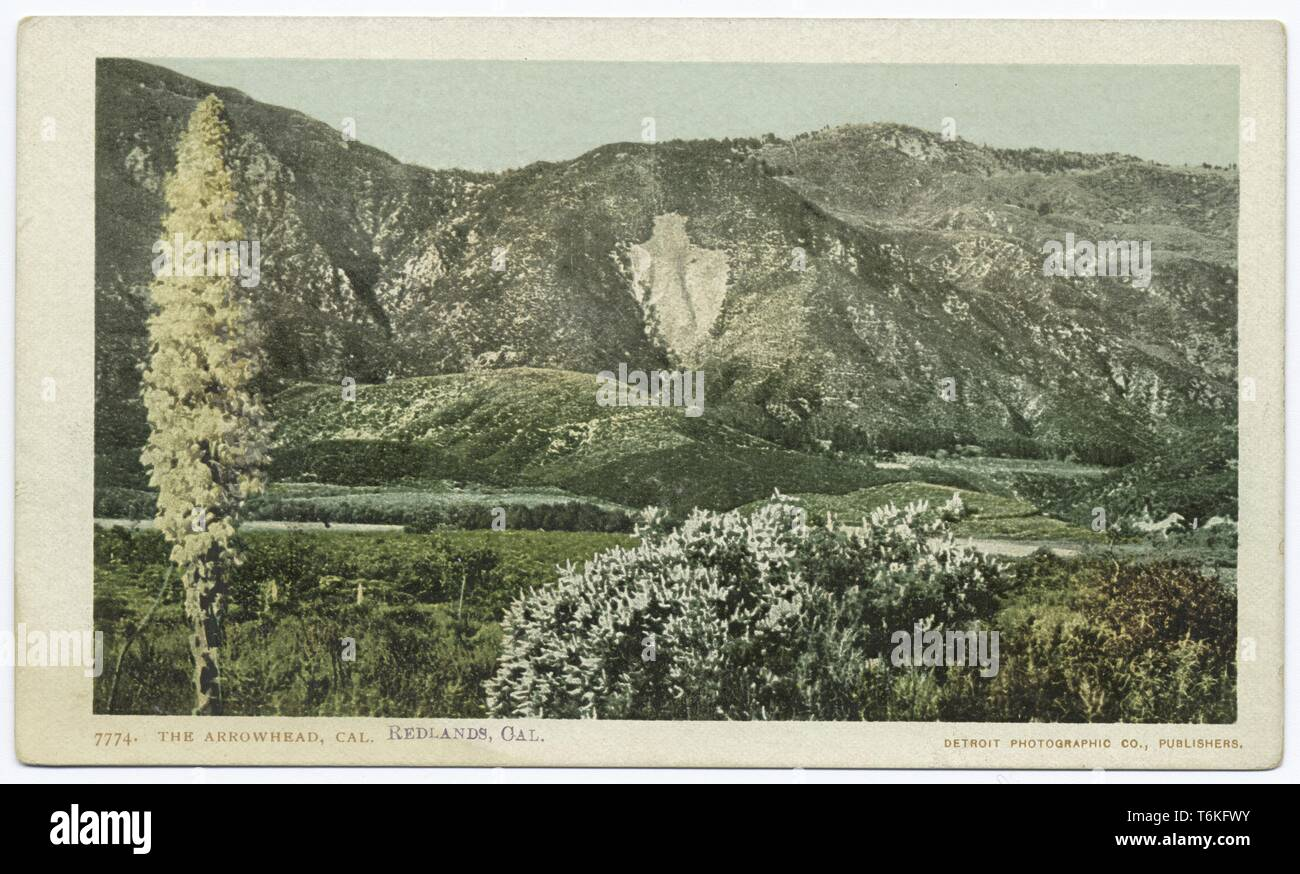 Postcard with a color image depicting a view of the San Bernadino Mountains, with the pale-colored, quartz outline of the arrowhead landmark visible on the mountain at center, and with low, green hills, a body of water, and foliage in the foreground; located near the city of San Bernardino, in the Inland Empire, California; published by the Detroit Photographic Company, 1914. From the New York Public Library. () - Stock Image