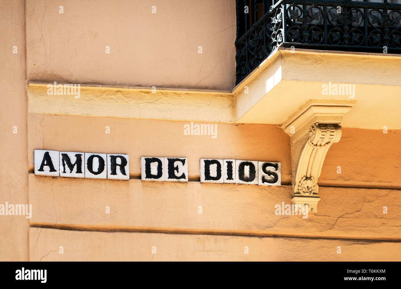 Street sign on the side of a building in Seville, Amor de Dios. The street name means Love of God - Stock Image