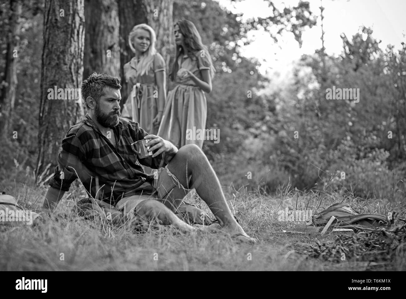 Bearded man drink tea at bonfire with women on blurred background. Hipster with beard sit at campfire. Friends enjoy camping in forest. Summer - Stock Image
