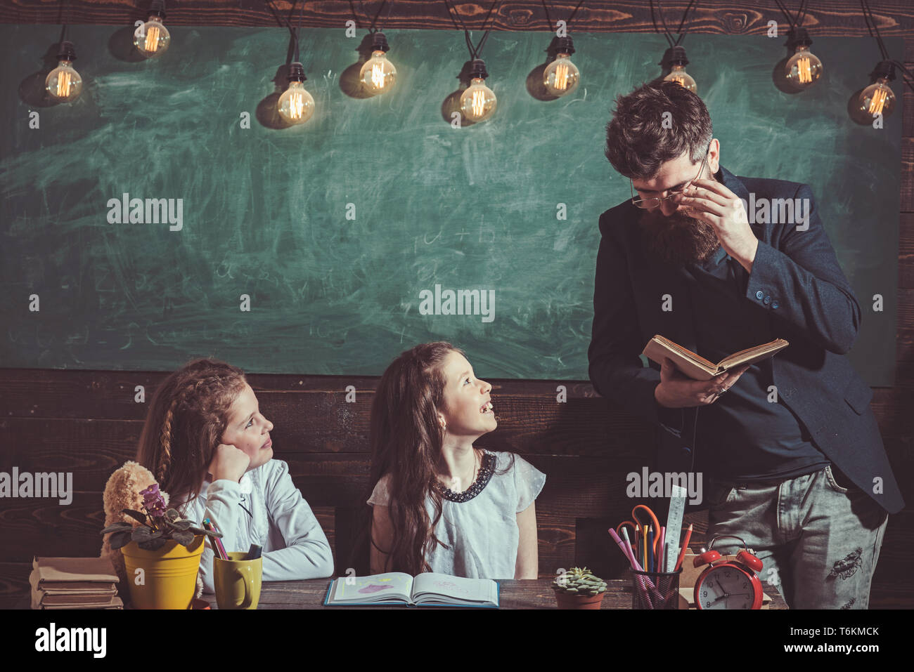 Teacher and schoolgirls on classroom background. Home schooling and back to school concept. Kids and tutor with smiling faces. Girls and bearded man - Stock Image
