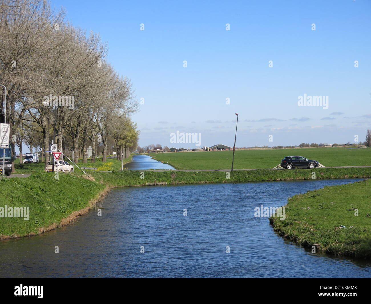 View of the flat landscape and canals as drainage measures in North Holland; a sunny spring day in Edam, North Holland Stock Photo