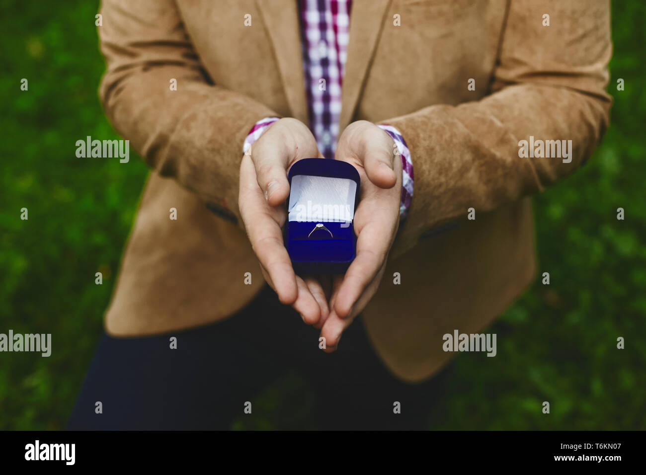 Box with stylish gold wedding rings in male hands of the handsome young man, proposal of marriage - Stock Image