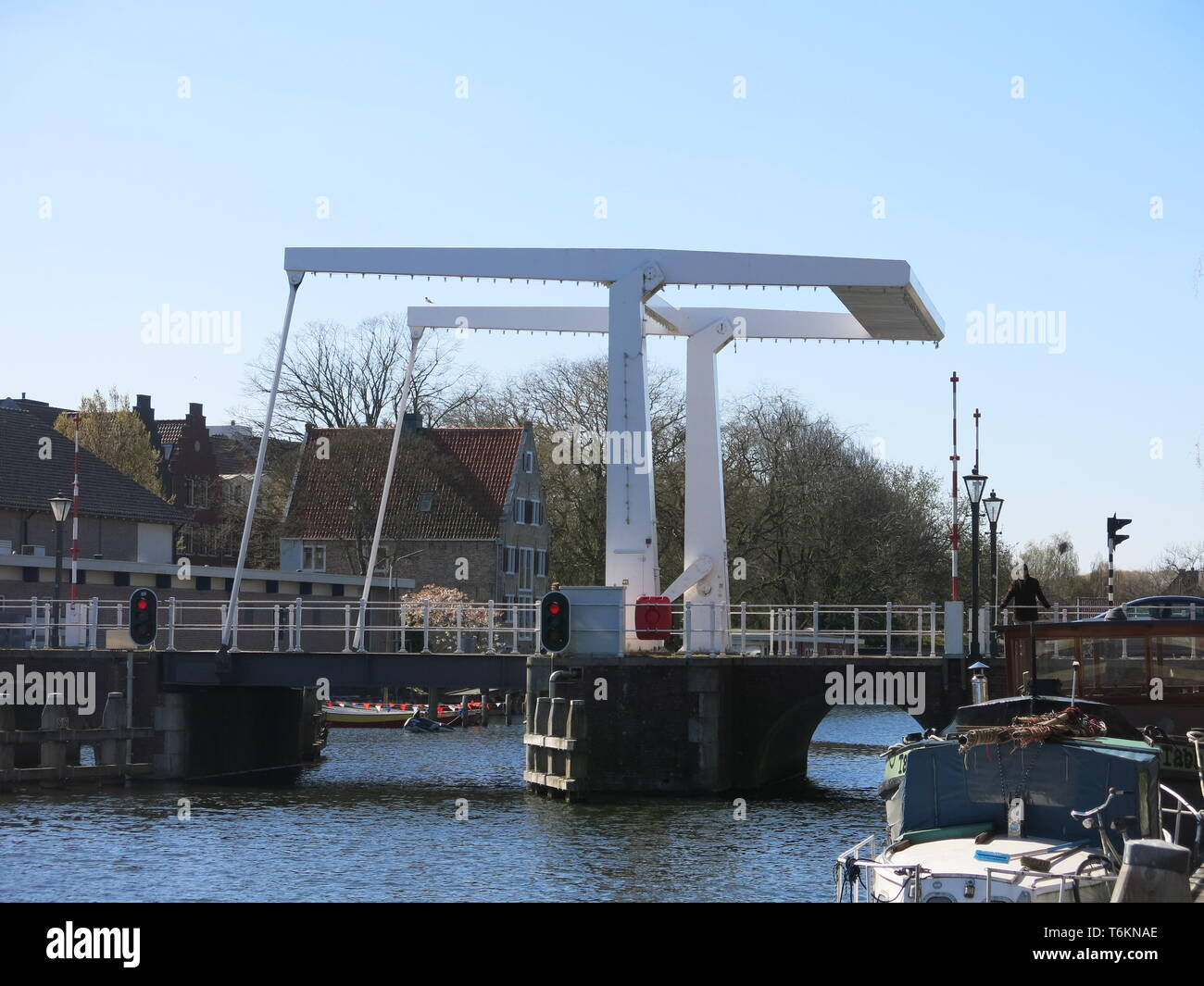 View of a typically Dutch white bascule bridge crossing the canal at Enkhuizen, a pretty coastal town in North Holland; April 2019 - Stock Image