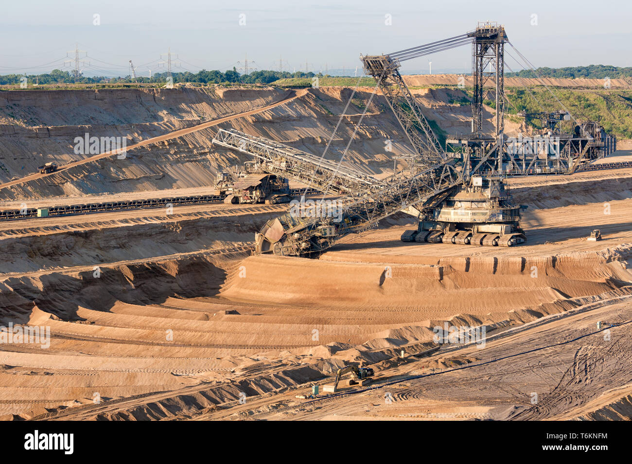 Brown coal open pit landscape with digging excavator in Germany Stock Photo