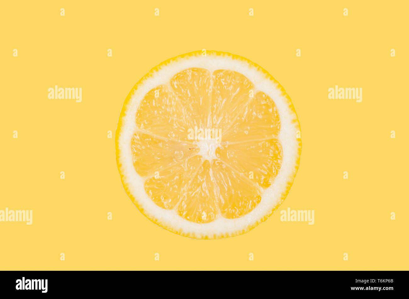 Fresh lemon slice on pastel yellow background Stock Photo