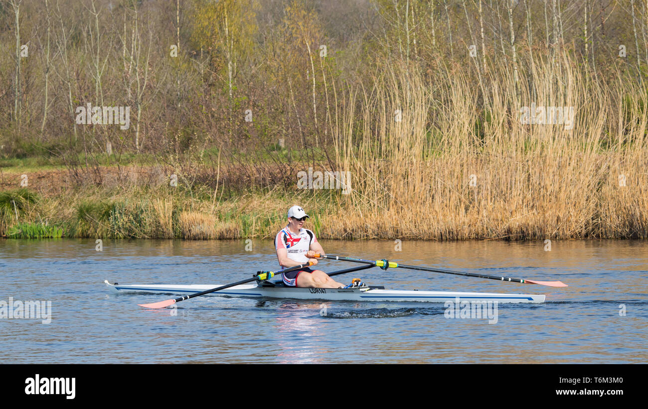 Male rower in canal. Rowing is a non-weight bearing sports that exercises major muscle groups like quads, biceps, triceps, glutes and abdominal muscle. - Stock Image